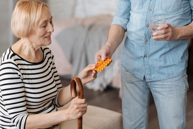 Ради нашего же блага, дорогая. красивая хрупкая старшая женщина сидит на кровати, пока ее муж приносит ей лекарство и стакан воды для его приема