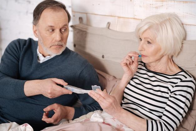 회복을 위해. 그녀의 노인 남편이 보유한 경우에서 약을 복용하는 아픈 할머니의 닫습니다.