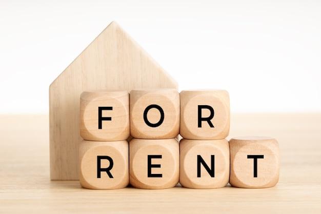 家賃のコンセプトについて。不動産市場。テキストと家のアイコンと木製のブロック。スペースをコピーします。 Premium写真