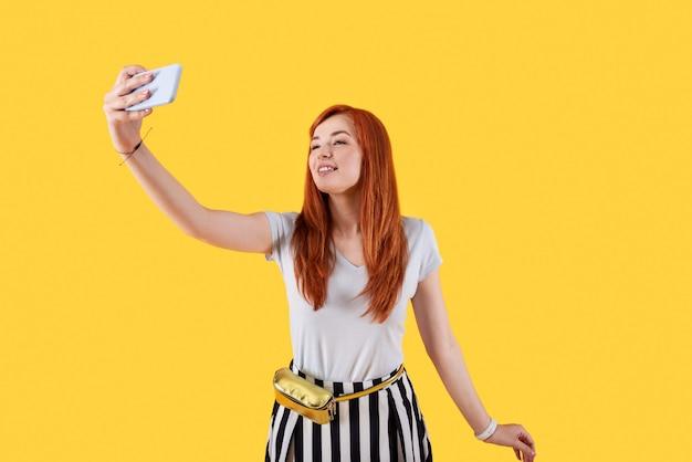 소셜 네트워크 용. 소셜 네트워크를 위해 사진을 찍는 동안 셀카를 복용하는 좋은 젊은 여자
