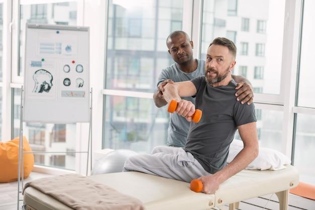 強さのために。物理的な運動をしながら医療ソファに座っているスマートなひげを生やした男