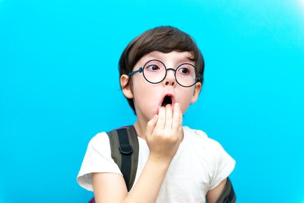 初めて学校に。親指で幸せな笑みを浮かべて男の子。小学生の制服姿の子供。屋内で青い壁に幼児。