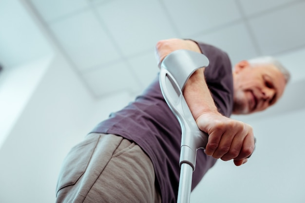 ウォーキング用。松葉杖を持って歩く男性の手の選択焦点