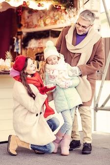 당신을 위해. 그녀의 부모 사이에 서있는 동안 그녀의 얼굴에 미소를 유지하는 친절한 소녀