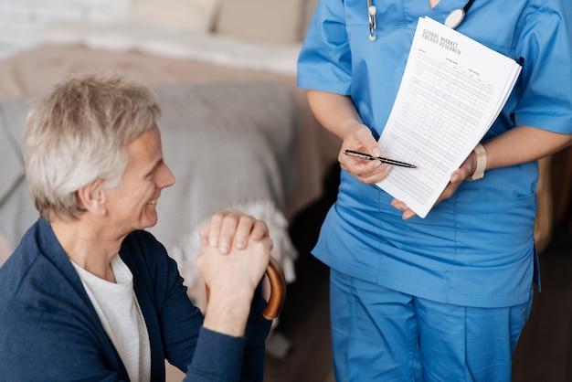 당신의 고려를 위해. 사랑스럽고 돌보는 의사가 일부 데이터를 시연하고 노인 신사가 치료의 모든 조건을 이해하도록합니다.