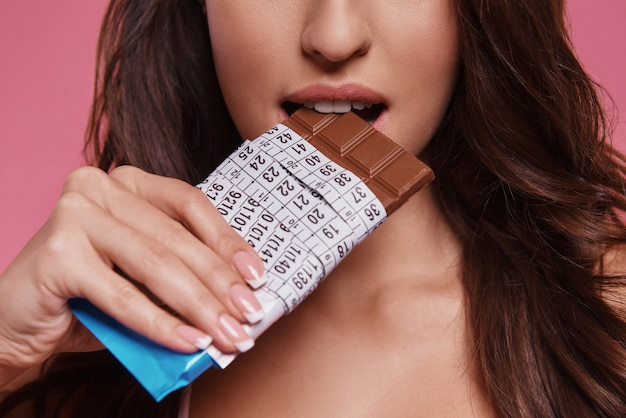금지된 음식입니다. 분홍색 배경에 서서 측정 테이프에 싸인 초콜릿을 먹는 젊은 여성의 클로즈업
