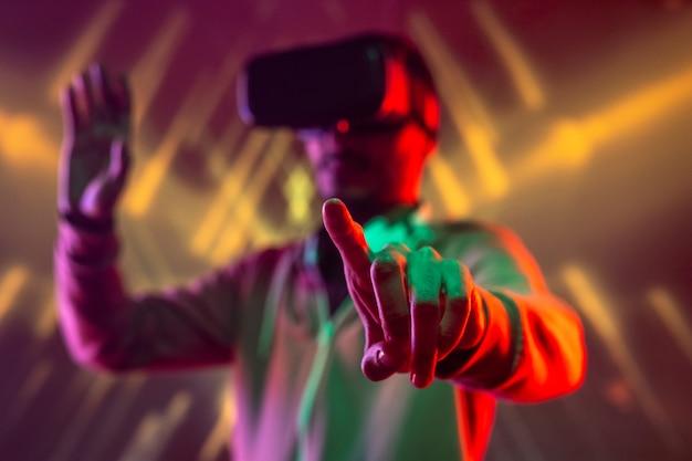 拡張現実で旅行中に仮想ボタンを押すか、ディスプレイに触れるvrヘッドセットを持つ若い男の人差し指