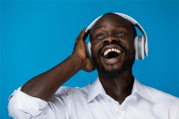 Foreground bearded smiling afroamerican man with open eyes looking up is holding by one hand big headphones