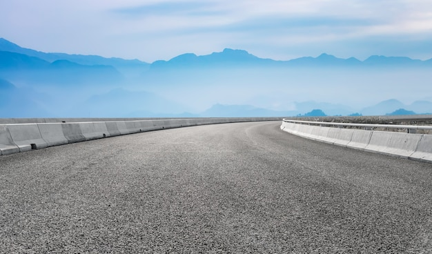 Foreground empty road and distant mountain background