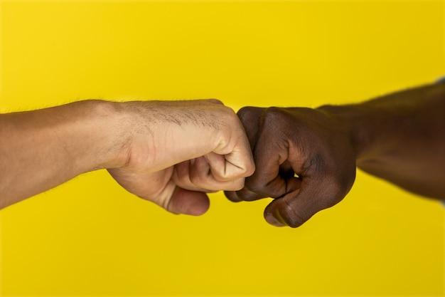 Foreground european and afroamerican hand to hand clenched into fists