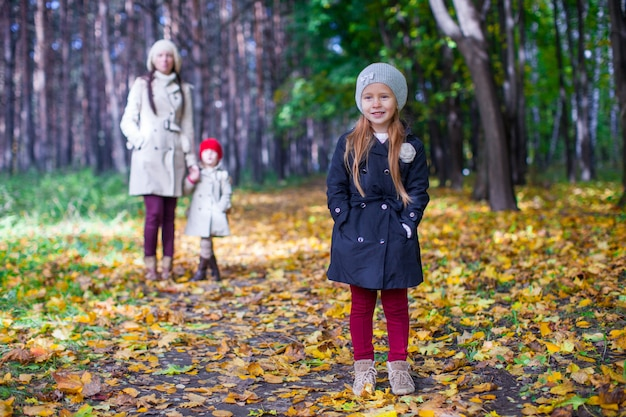 In the foreground is a beautiful sweet girl behind her mother and sister at autumn park