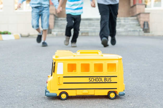 In the foreground is a yellow toy school bus with children running towards it in the background back to school concept