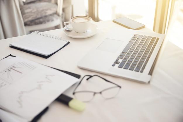 Передний план объектов на рабочем месте: очки, диаграммы, ноутбук, тетрадь
