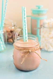 In the foreground of photos with a jar of hot cocoa and cocktail straws.