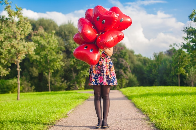 In the foreground, red balloons, followed by young woman at beautiful dress