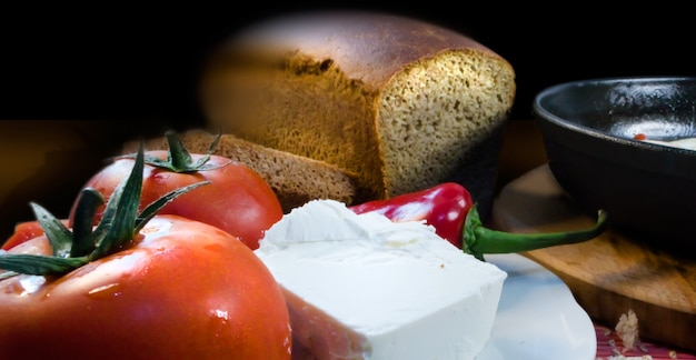 Foreground with tomatoes, cheese, pepper, bread, and a frying pan on a dark vintage background.
