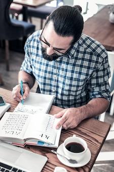 外国語。外国語のアルファベットを勉強している成熟した黒髪の男の上面図
