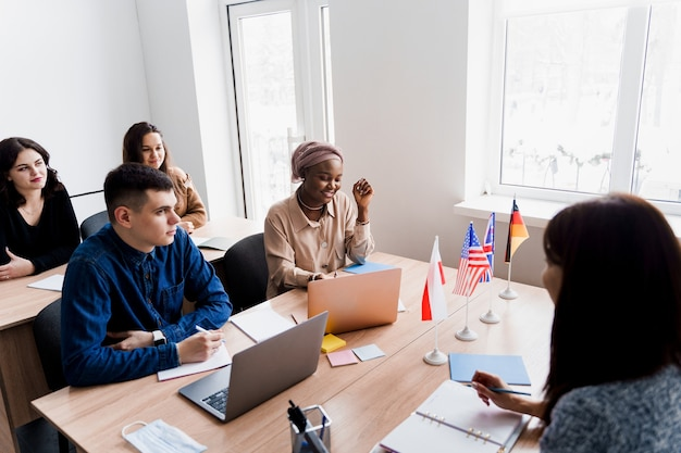 여고생과 함께하는 외국인 학교 개인 학습. 교사가 노트북을 사용하여 모국어 문법을 설명합니다. 튜터와 함께 시험을 준비합니다. 영어, 영국, 독일어 및 폴란드 플래그가 앞에 있습니다.