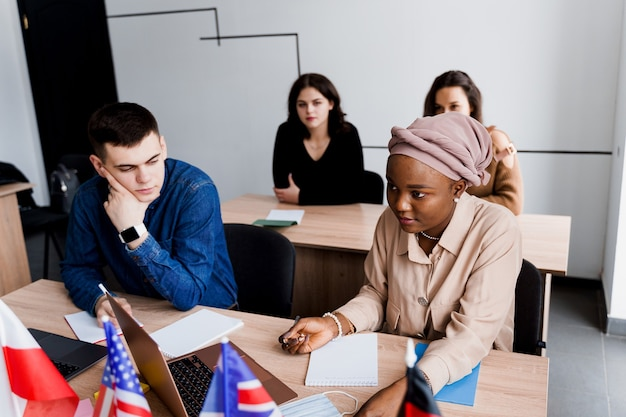女子校生との外国人学校私立学習。先生はノートパソコンを使って母国語の文法を説明します。家庭教師との試験の準備。英語、イギリス、ドイツ、ポーランドの旗が前にあります。