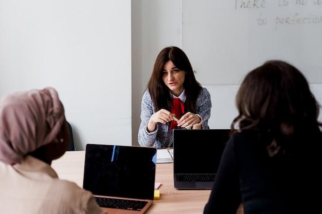 女子校生との外国人学校私立学習。先生はノートパソコンを使って母国語の文法を説明します。家庭教師との試験の準備。