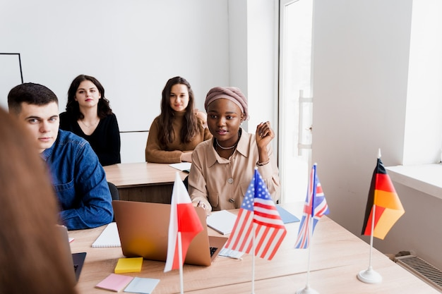 Foreign school private study with a school woman. teacher explain grammar of native language using laptop. prepearing to exam with tutor. english, british, german and poland flags in front.