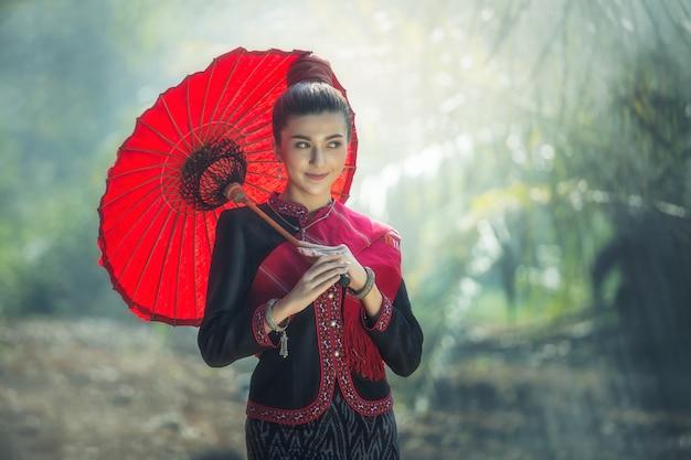 赤い傘と赤い胸の布で典型的な(伝統的な)身に着けている外国の女性