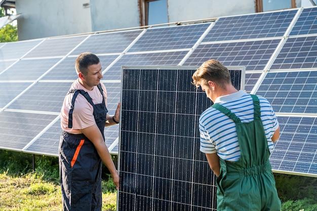 太陽光発電パネルを設置する職長とエンジニア。代替グリーンエネルギー