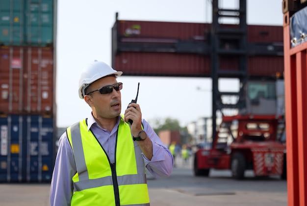 Бригадир контролирует погрузку контейнеров в ящик с грузового корабля для импорта и экспорта, транспортировка