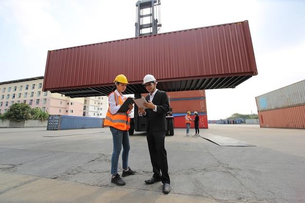 Бригадир контролирует погрузку контейнеров в ящик с грузового корабля для импорта-экспорта. работник контейнерного склада.