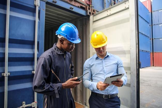 Бригадир контролирует погрузку грузовых контейнеров в морской порт отправления и прибытия грузового судна