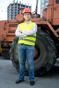 Foreman in hardhat posing next to bulldozer with crossed hands