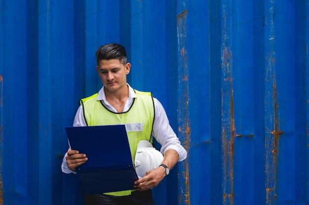 Бригадир, держащий документы, ходьба и проверка ящика контейнеров с грузового судна для экспорта и импорта