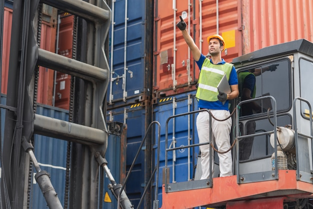 Foreman holding laptop and point to position loading containers box at cargo container shipping