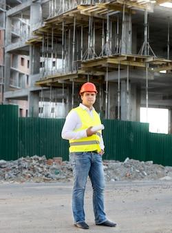 재킷과 헬멧에 포먼이 비계에서 건물에 대해 포즈를 취함