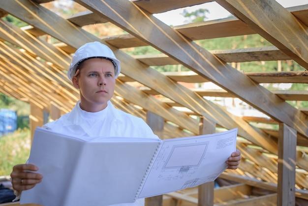 Бригадир в белой одежде осматривает строительство