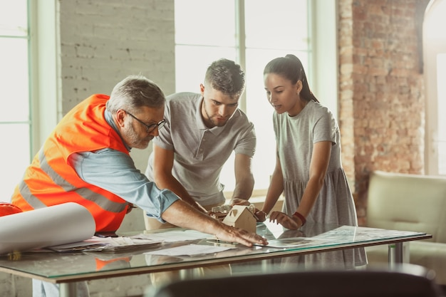 フォアマンまたはアキテクトエンジニアは、若いカップルに将来の家、オフィス、または店舗の設計計画とモデルを示します。ファサード、室内装飾、家のレイアウトについて話し合うために建設事務所で会合。