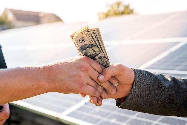 Foreman receives a dollar salary from a businessman after work on the installation of solar panels