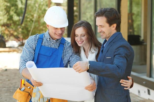 Бригадир показывает план дизайна дома молодой паре