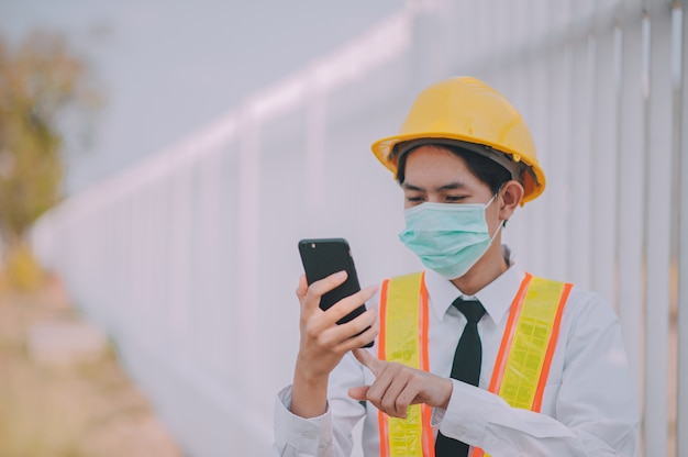 Foreman using mobile smart phone on site construction