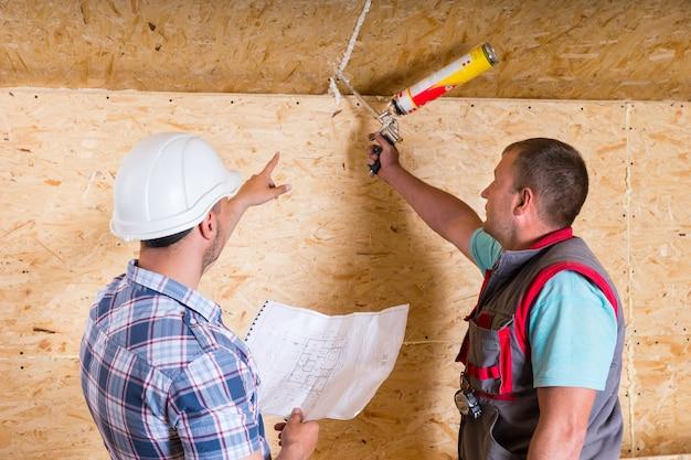 새 집에서 미완성 목재 천장의 이음매에 코킹을 적용하는 방법을 작업자에게 지시하는 흰색 안전모를 쓰고 건물 도면을 들고 있는 감독