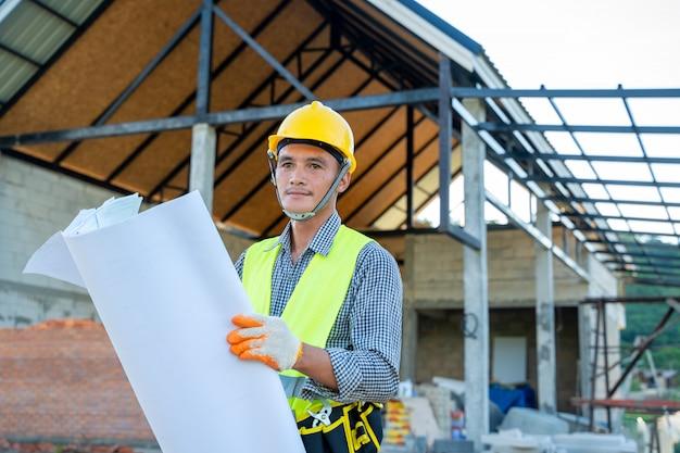 青写真を持つ職長は、建設現場の建物のプロジェクトに取り組んでいます。