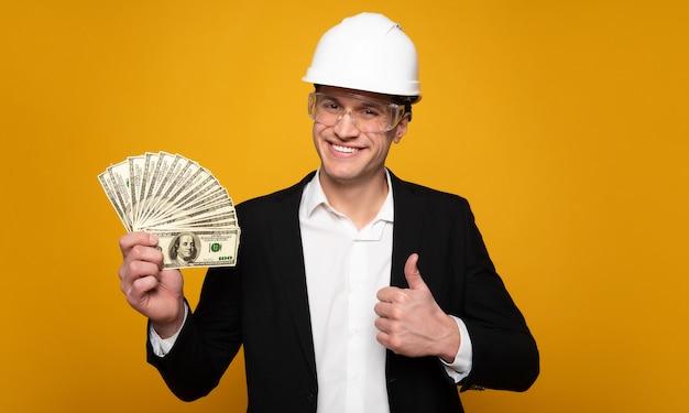 フォアマンの給料。スーツと建設用ヘルメットをかぶった幸せな若者のクローズアップ写真。彼は右手に現金の札束を持って親指を立てています。