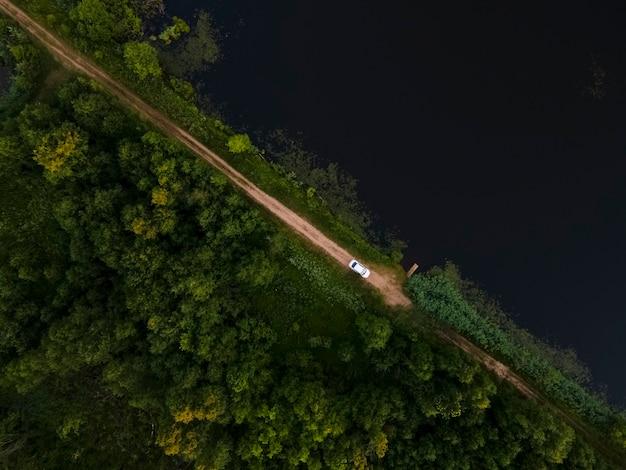 森と湖の空撮風景それらの間に白い車が乗る田舎道があります