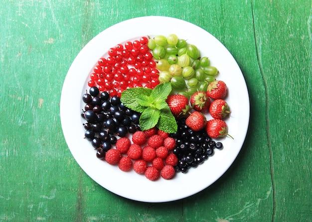 컬러 나무 표면에 접시에 숲 딸기