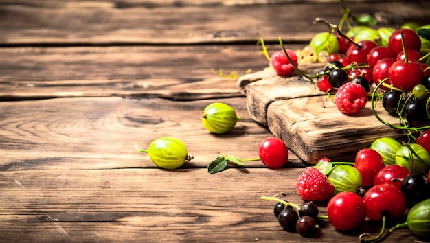 Лесные ягоды на доске. на деревянном столе.