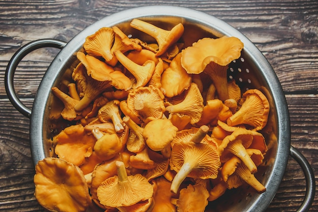 木製のテーブルの森のアンズタケ。調理用の新鮮なキノコ。