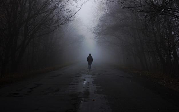 Лес в тумане. человек идет по туману. темный туманный лес с волшебной атмосферой