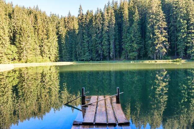 푸른 물, 나무 다리, 아침 햇살, 빛나는 태양이 있는 산속의 숲 호수