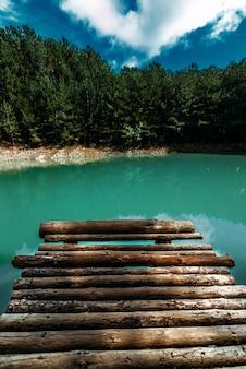 Лесное озеро с деревянным пирсом, вертикальный вид. красивое бирюзовое озеро с деревянной пристанью в хвойном лесу. изумрудное лесное озеро. заставка для вашего смартфона. пейзажная фотография на вашем телефоне