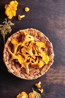 숲 버섯 살구와 나무 오래 된 배경에 숲 이끼. 갈색 질감 배경 위에 등나무 접시 그릇에 익지 않은 날. 조롱. 평면도.